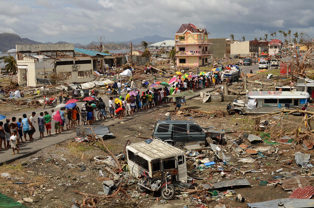 Description of . Survivors form a queue to receive relief goods at a devastated coastal area on November 16, 2013 in Leyte, Philippines. (Photo by Dondi Tawatao/Getty Images)