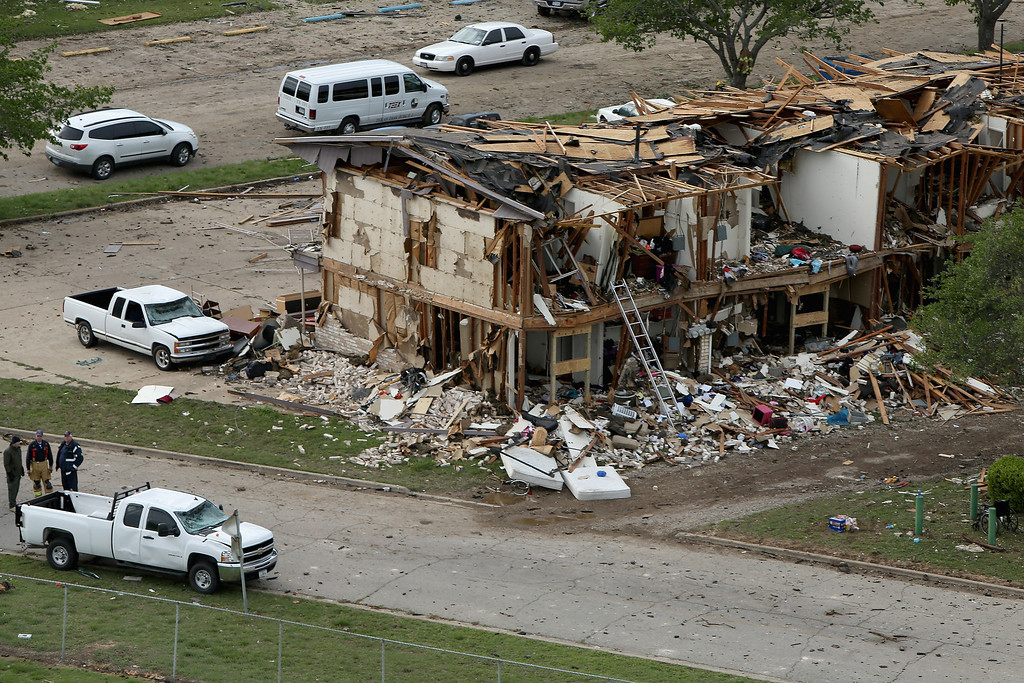 Description of . WEST, TX - APRIL 18:  Search and rescue workers comb through what remains of a 50-unit apartment building the day after an explosion at the West Fertilizer Company destroyed the building April 18, 2013 in West, Texas. According to West Mayor Tommy Muska, around 35 people, including 10 first responders, were killed and more than 150 people were injured when the fertilizer company caught fire and exploded, leaving damaged buildings for blocks in every direction.  (Photo by Chip Somodevilla/Getty Images)