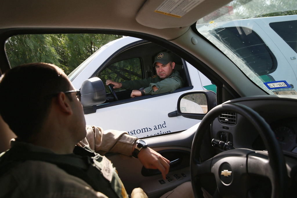 Description of . MISSION, TX - APRIL 11:  A U.S. Office of Air and Marine (OAM) agent (L), and a U.S. Border Patrol agent talk while on patrols near the U.S.-Mexico border on April 11, 2013 in McAllen, Texas.  According to the U.S. Border Patrol, undocumented immigrant crossings have increased more than 50 percent in the Rio Grande Valley sector in the last year. Border Patrol agents say they have also seen an additional surge in immigrant traffic since immigration reform negotiations began this year in Washington D.C. Proposed refoms could provide a path to citizenship for many of the estimated 11 million undocumented workers living in the United States.  (Photo by John Moore/Getty Images)