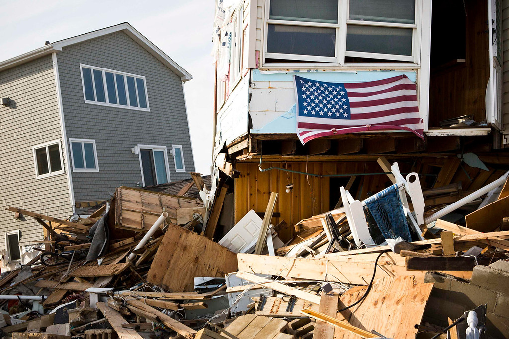 Description of . A U.S. flag hangs from a home that was damaged by Hurricane Sandy, in the Ortley Beach area of Toms River, New Jersey November 28, 2012. The storm made landfall along the New Jersey coastline on October 29, 2012 - one month ago tomorrow. REUTERS/Andrew Burton