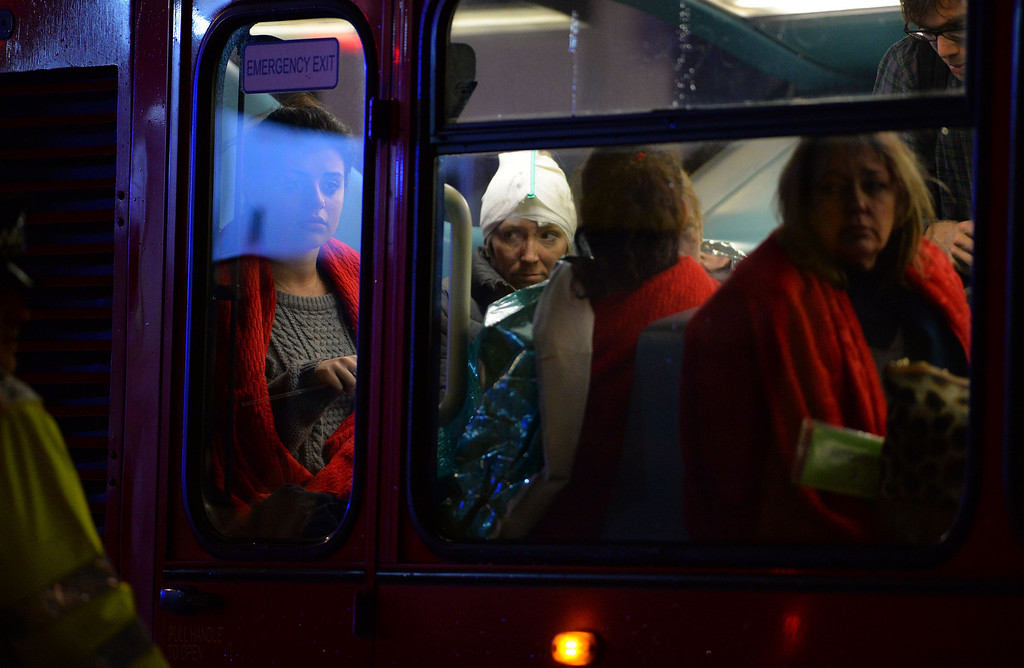 . Injured people sit wrapped in emergency blankets on a London bus used for casualties following a ceiling collapse at a theatre in Central London on December 19, 2013.    AFP PHOTO/LEON NEAL/AFP/Getty Images