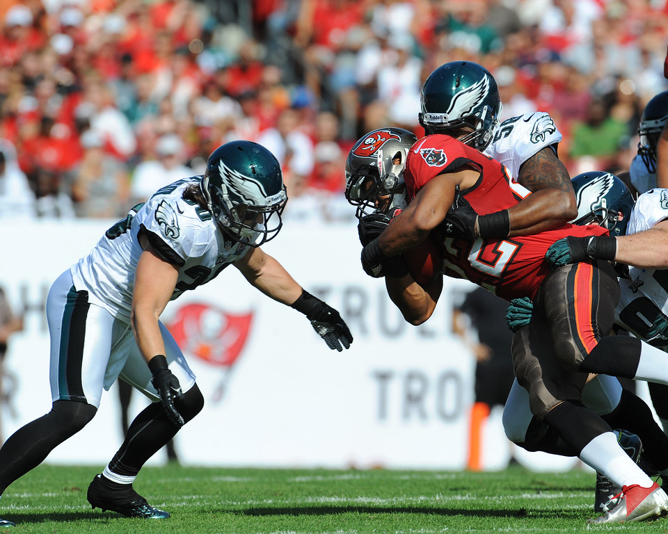 . TAMPA, FL - DECEMBER 9: Linebacker Trent Cole #58 of the Philadelphia Eagles tackles running back Dough Martin #22 of the Tampa Bay Buccaneers  December 9, 2012 at Raymond James Stadium in Tampa, Florida. The Eagles won 23 -  21. (Photo by Al Messerschmidt/Getty Images)