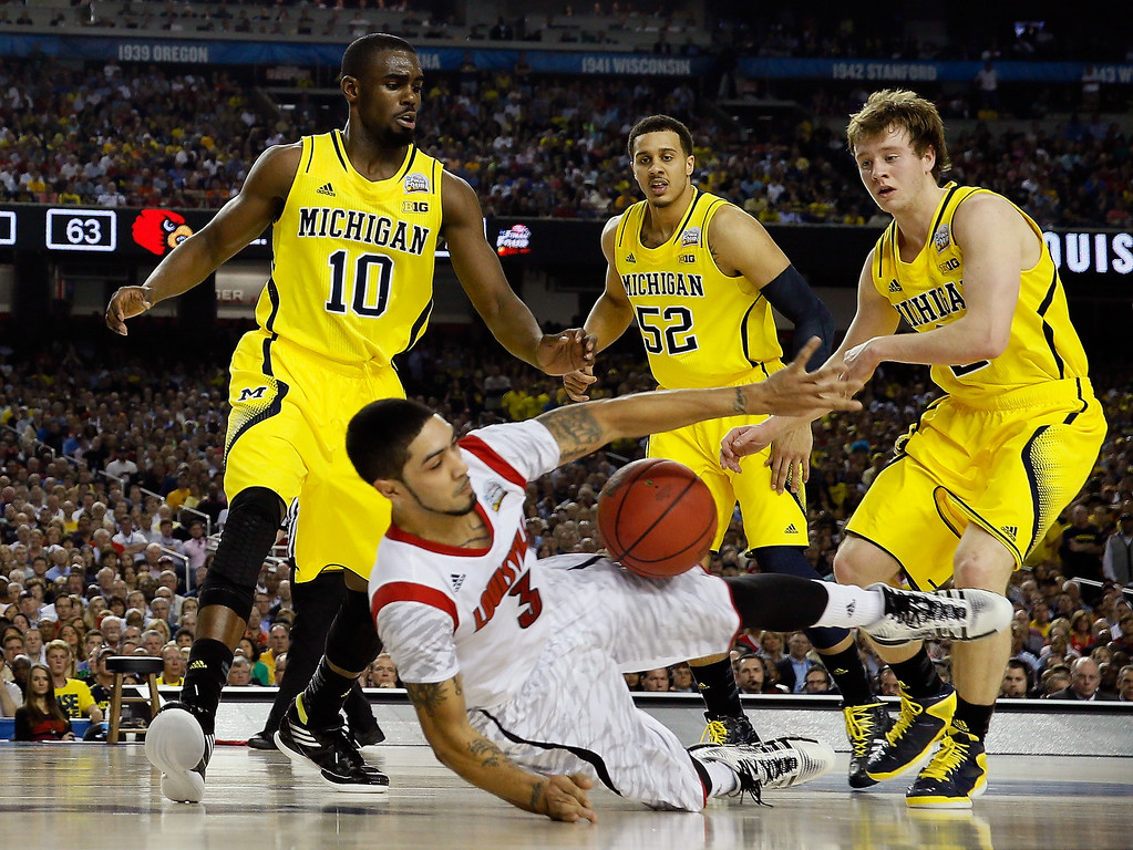 Description of . Peyton Siva #3 of the Louisville Cardinals attempts to control the ball in the second half as he falls down against Tim Hardaway Jr. #10, Jordan Morgan #52 and Spike Albrecht #2 of the Michigan Wolverines during the 2013 NCAA Men's Final Four Championship at the Georgia Dome on April 8, 2013 in Atlanta, Georgia.  (Photo by Streeter Lecka/Getty Images)