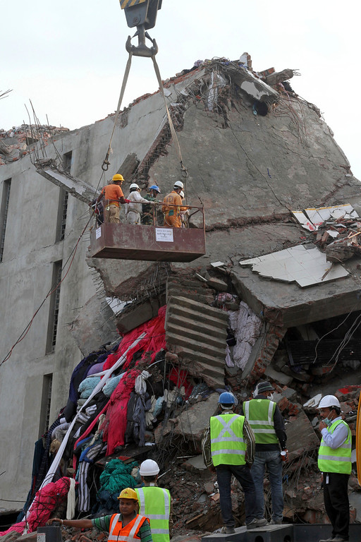 Description of . Bangladeshi authorities use machinery lift search teams as they clear the broken and crushed concrete slabs of a building that collapsed in Savar, outskirts of Dhaka, Bangladesh, Tuesday, April 30, 2013. (AP Photo/Palash Khan)