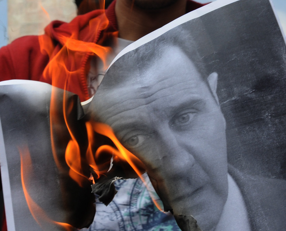 Description of . A protestor burns a portrait of Syrian President Bashar al-Assad during a demonstration after Friday prayers on April 29, 2011 in Istanbul against the regime of al-Assad and the deadly crackdown on opposition protests. About 1,000 people demonstrated in Istanbul Friday to denounce a bloody crackdown on protests in Syria, calling for President Bashar al-Assad's departure.  Following Friday prayers at an ancient mosque, the crowd, including Syrians based in Turkey's largest city, staged a march, chanting slogans against Assad and burning his portraits, an AFP reporter said. BULENT KILIC/AFP/Getty Images
