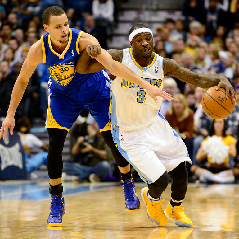Description of . Golden State Warriors point guard Stephen Curry (30) fouls Denver Nuggets point guard Ty Lawson (3) during the first half at the Pepsi Center on Sunday, January 13, 2013. AAron Ontiveroz, The Denver Post