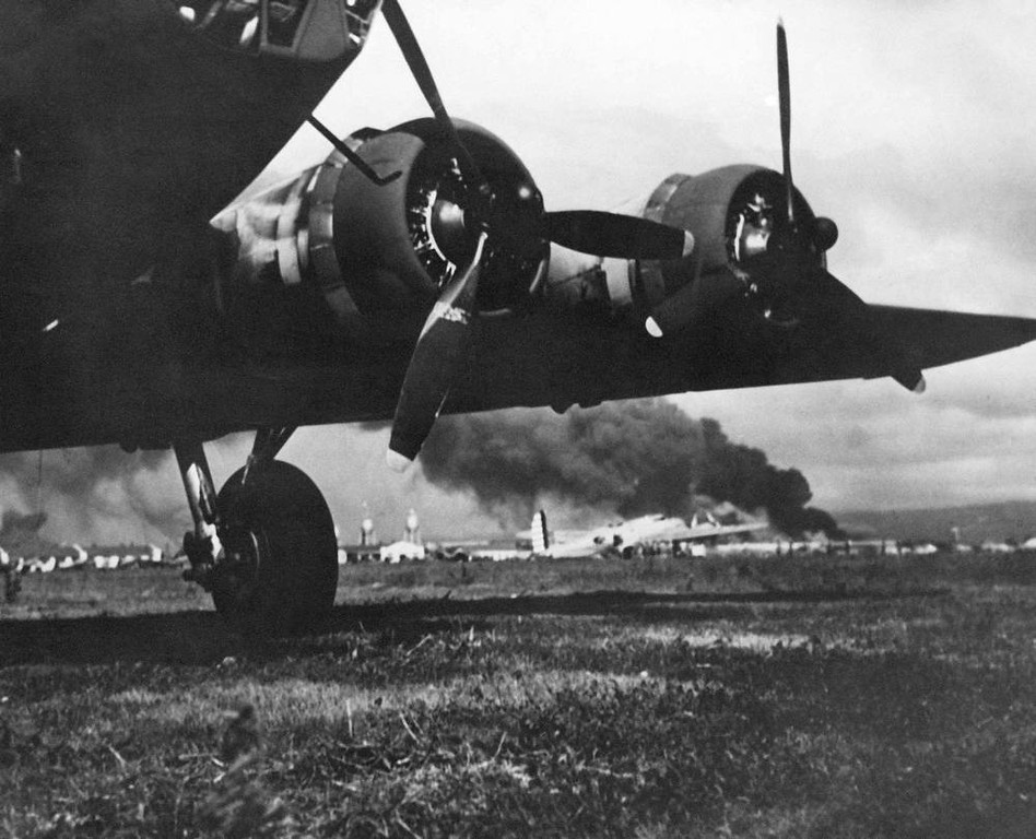 Description of . In this photo provided by the U.S. Army, blazing from Japanese bombing attack on the Army's Hickam Field, B-17 Army bombers seen behind two motors of one of the bombers which escaped damage, Dec. 12, 1941. (AP Photo/U.S. Army)