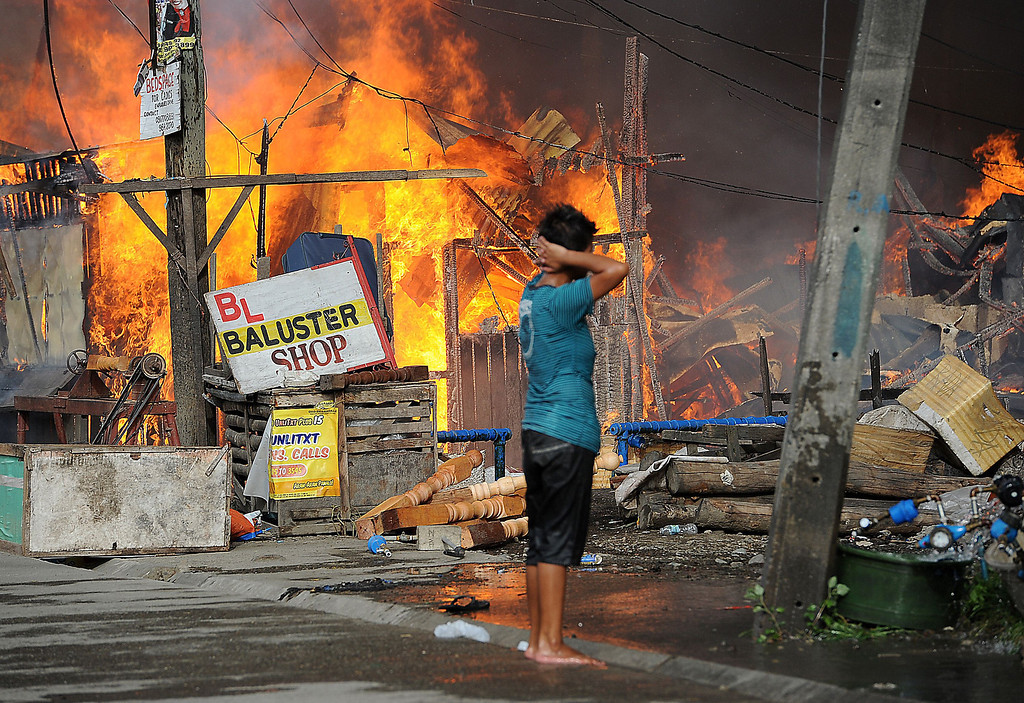 Description of . A resident looks at burning houses during a fire fight between government forces and Muslim rebels as stand-off entered its fourth day in Zamboanga City on the southern island of Mindanao on September 12, 2013.   AFP PHOTO/TED ALJIBE/AFP/Getty Images