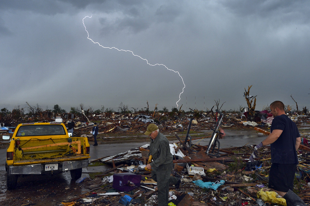 Description of . Lightning strikes during a thunder storm as tornado survivors search for salvagable stuffs at their devastated home on May 23, 2013, in Moore, Oklahoma. Severe thunderstorms barreled through this Oklahoma City suburb at dawn Thursday, complicating clean-up efforts three days after a powerful tornado killed 24 people and destroyed 2,400 homes. More rain was forecast to fall on Moore, soaking the disaster zone where residents had just the day before, under clear blue skies, started picking through the rubble of their destroyed houses to recover personal effects. JEWEL SAMAD/AFP/Getty Images