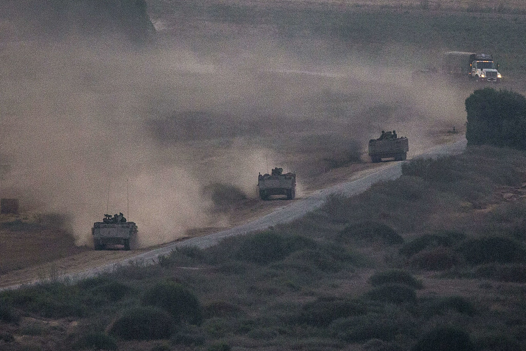 Description of . A picture taken from the southern Israeli Gaza border shows Israeli army armored personnel carriers (APC) rolling along the border with the Gaza strip, on July 21, 2014. Israeli forces killed more than 10 Gaza militants who had infiltrated southern Israel today, the army said, later announcing it had lost four soldiers in that battle. AFP PHOTO / JACK GUEZ/AFP/Getty Images