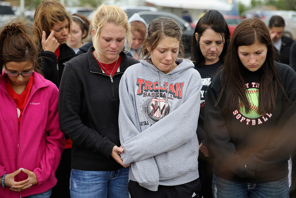 Description of . WEST, TX - APRIL 18:  West High School senior students (L-R) Brittany Singh, Kelsey Hoelscher, Ashton Uptmor and Nicole Hutyra pray for the victims and survivors the day after the West Fertilizer Company explosion April 18, 2013 in West, Texas. Hoelscher's uncles, Bob and Doug Snokhous, were volunteer fire fighters who are presumed dead after the fertilizer company caught fire and exploded, injuring more than 160 people and leaving damaged buildings for blocks in every direction.  (Photo by Chip Somodevilla/Getty Images)
