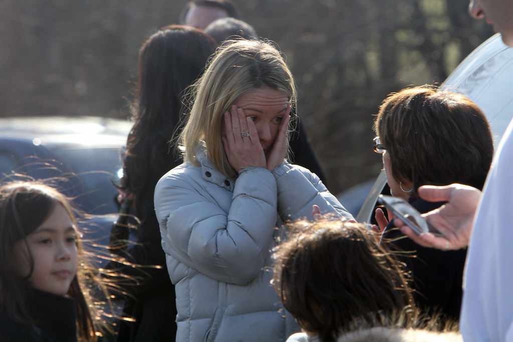 Description of . A woman weeps as she arrives to pick up her children at the Sandy Hook Elementary School in Newtown, Conn. where authorities say a gunman opened fire, leaving 27 people dead, including 20 children, Friday, Dec. 14, 2012. (AP Photo/The Journal News, Frank Becerra Jr.)