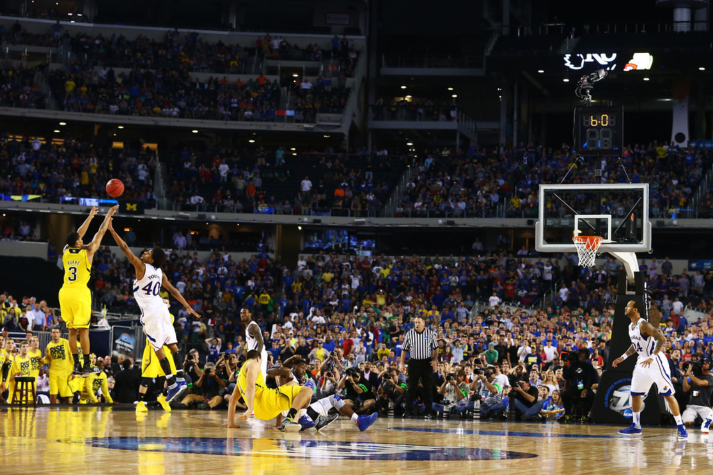 Description of . ARLINGTON, TX - MARCH 29:  Trey Burke #3 of the Michigan Wolverines shoots a game tying three pointer in the final seconds of the second half over Kevin Young #40 of the Kansas Jayhawks during the South Regional Semifinal round of the 2013 NCAA Men\'s Basketball Tournament at Dallas Cowboys Stadium on March 29, 2013 in Arlington, Texas.  (Photo by Ronald Martinez/Getty Images)