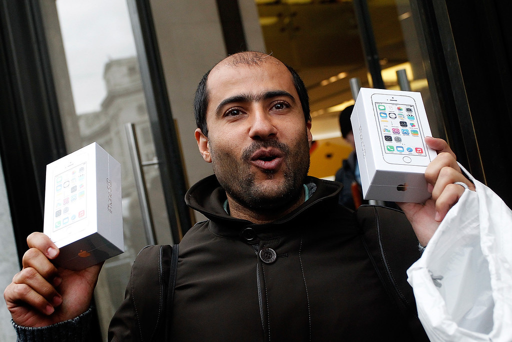 Description of . An ecstatic iPhone fan clutches two new iPhone 5S\'s as he leaves the Apple store with his purchases, on Regent Street on September 20, 2013 in London, England.  (Photo by Mary Turner/Getty Images)
