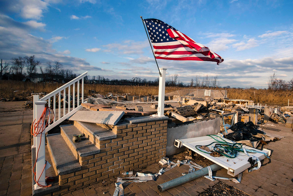 Description of . A U.S. flag flies over the foundation of a home destroyed by the storm surge of superstorm Sandy in the Staten Island borough neighborhood of Oakwood in New York, November 28, 2012.  REUTERS/Lucas Jackson