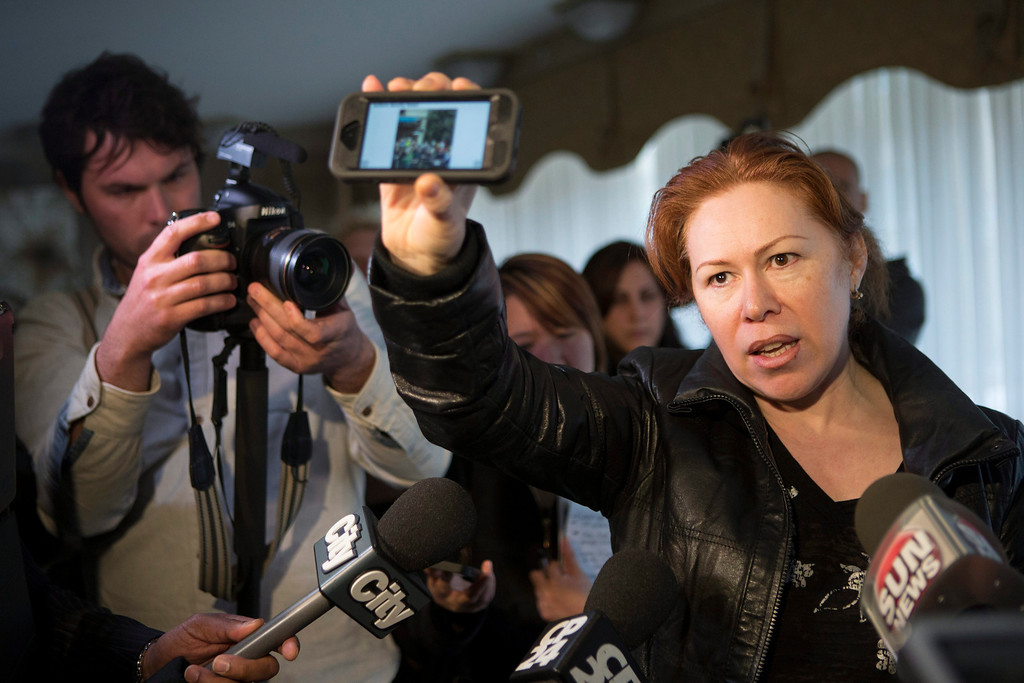 Description of . Maret Tsarnaeva, an aunt of the two suspects in the Boston Marathon bombing, holds a reporter's smart phone which displays a scene from the bomb site, as she speaks to journalists in the lobby of her apartment building in Toronto on Friday April 19, 2013.  Tamerlan Tsarnaev, a 26-year-old who had been known to the FBI as Suspect No. 1 and was seen in surveillance footage in a black baseball cap, was killed overnight, officials said. His brother, a 19-year-old college student who was dubbed Suspect No. 2 and was seen wearing a white, backward baseball cap in the images from Monday's deadly bombing at the marathon finish line, escaped. (AP Photo/The Canadian Press, Chris Young)