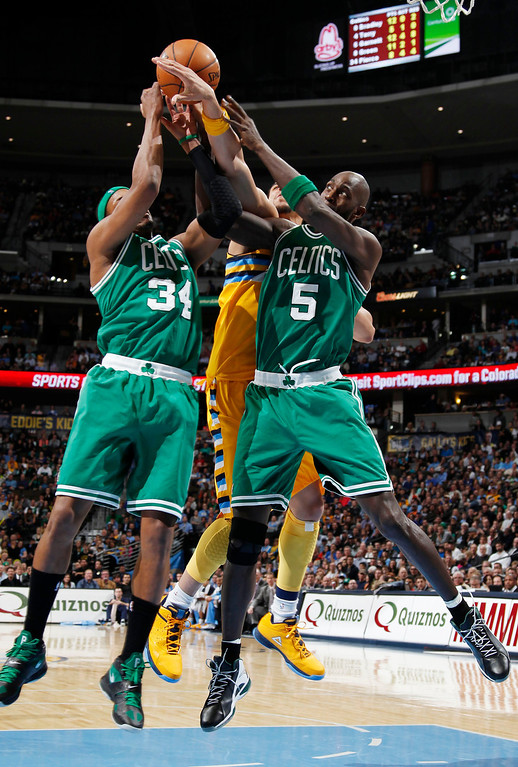Description of . Boston Celtics forwards Paul Pierce, left, and Kevin Garnett, right, box out Denver Nuggets forward JaVale McGee for a rebound during the fourth quarter of the Nuggets' 97-90 victory in an NBA basketball game in Denver on Tuesday, Feb. 19, 2013. (AP Photo/David Zalubowski)