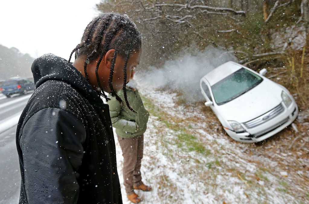 Description of . Jesse Hatcher looks over his crashed car after he says another motorist caused him to lose control of his car and spin out off I-20 West near Conyers, Ga.,  on Tuesday, Jan. 28, 2014. Light snow moved into parts of north Georgia by midmorning and began coating the metro Atlanta region by noon.  (AP Photo/Atlanta Journal-Constitution, Curtis Compton)