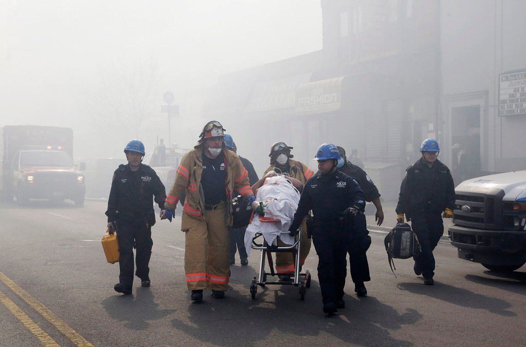 Description of . Rescue workers remove an injured person on a stretcher following a building explosion and collapse in East Harlem, Wednesday, March 12, 2014 in New York. (AP Photo/Mark Lennihan)