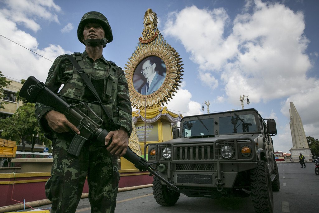 Description of . A Thai soldier stands in front of a portrait of Thai King Bhumibol Adulyadej as he patrols near government  buildings on May 23, 2014 in Bangkok, Thailand. The Army chief announced in an address to the nation that the armed forces were seizing power in a non-violent coup. Thailand has seen months of political unrest and violence which has claimed at least 28 lives. (Photo by Paula Bronstein/Getty Images)