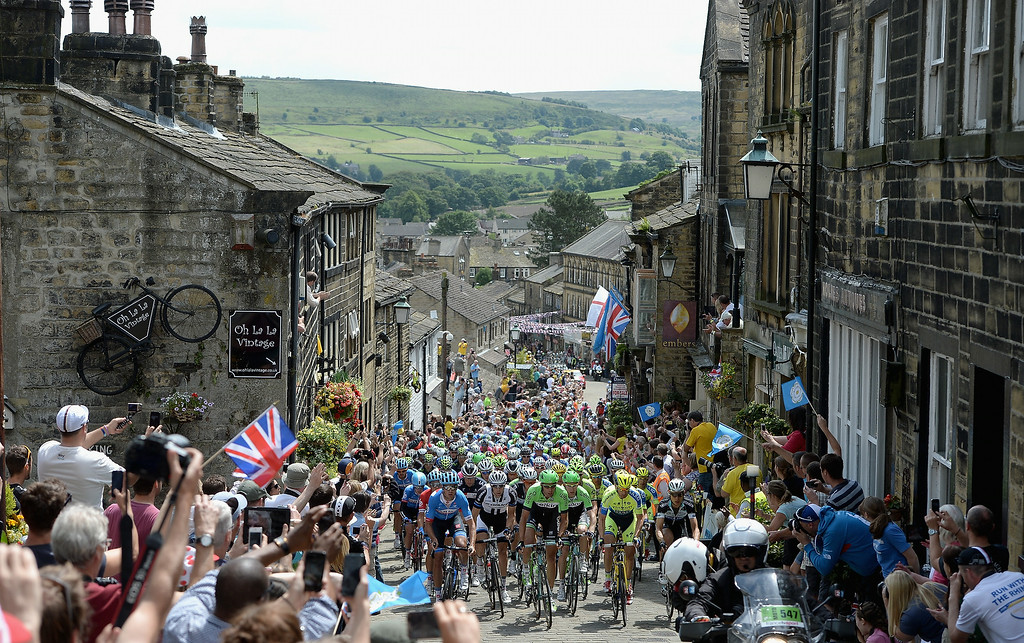 Description of . SHEFFIELD, ENGLAND - JULY 06:  The Peloton ride up Haworth High Street during Stage Two of Le Tour de France on July 6, 2014 in Haworth, England.  (Photo by Gareth Copley/Getty Images)