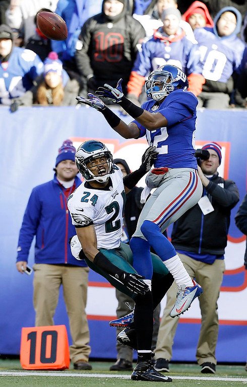 Description of . New York Giants wide receiver Rueben Randle (82) catches a pass as Philadelphia Eagles cornerback Nnamdi Asomugha (24) defends during the first half of an NFL football game on Sunday, Dec. 30, 2012, in East Rutherford, N.J. (AP Photo/Kathy Willens)