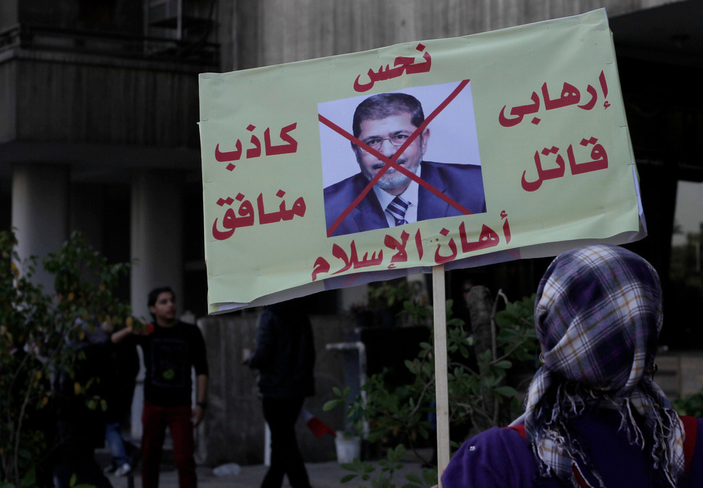 ". A woman carries a sign with a photo of Egyptian President Mohammed Morsi and Arabic that reads, ""jinx, terrorist killer, embarrassment to Islam. hypocritical liar,\"" during a march near Tahrir Square, Cairo, Egypt, Friday, Jan. 25, 2013. Egyptian opposition protesters are gathering in Cairo\'s Tahrir Square to mark the second anniversary of the uprising that toppled Hosni Mubarak\'s autocratic regime. (AP Photo/Nariman El-Mofty)"