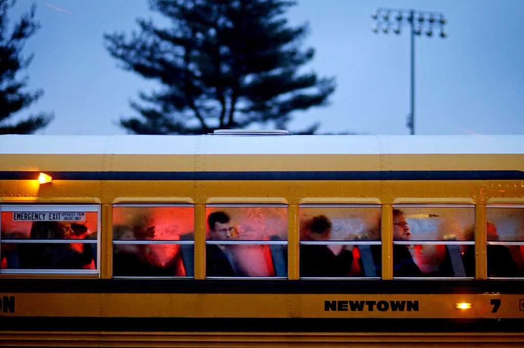 Description of . People arrive on a school bus at Newtown High School for a memorial vigil attended by President Barack Obama for the victims of the Sandy Hook Elementary School shooting, Sunday, Dec. 16, 2012, in Newtown, Conn. A gunman walked into Sandy Hook Elementary School in Newtown Friday and opened fire, killing 26 people, including 20 children. (AP Photo/David Goldman)