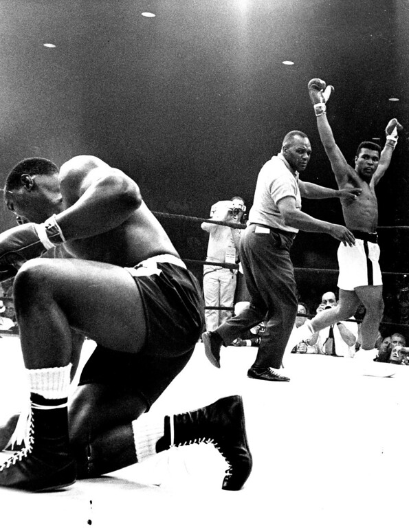 Description of . LEWISTON, MAINE:  Referee Joe Walcott guides heavyweight champion Cassius Clay to a neutral corner after Clay downed challenger Sonny Liston (struggling to his feet) in the first round of their championship bout here May 25th., 1965. Clay retained his crown by scoring a one-minute knockout victory over Liston in the controversial fight. Denver Post Library photo archive
