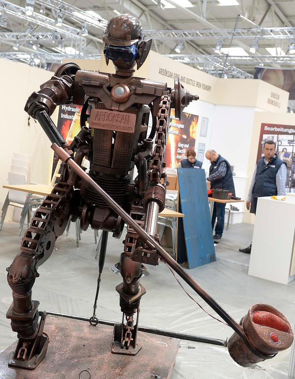 Description of . A robot figure is seen during preparations at the Hanover industrial fair in Hanover, April 7, 2013. The Hanover fair opens its doors to the public on April 8 and will end on April 12. REUTERS/Fabian Bimmer