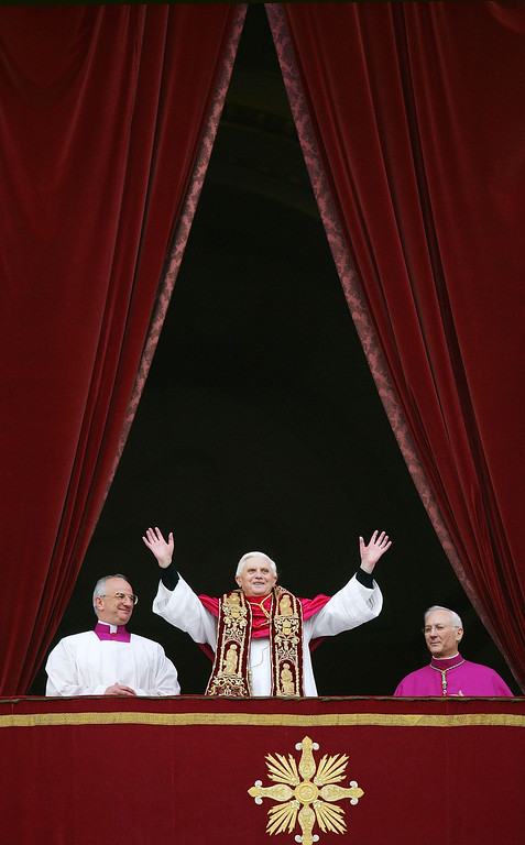 Description of . Pope Benedict XVI, Cardinal Joseph Ratzinger (C) of Germany, waves from a balcony of St. Peter's Basilica in the Vatican after being elected by the conclave of cardinals April 19, 2005 in Vatican City.  The 265th Pope will lead the world's 1 billion Catholics. (Photo by Mario Tama/Getty Images)