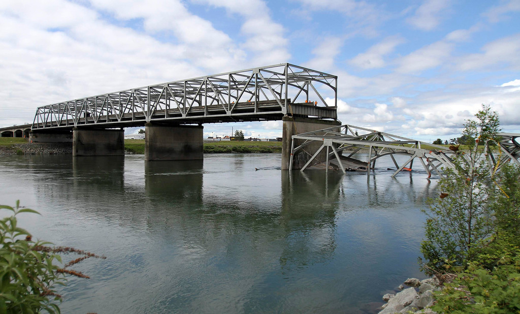 Description of . A span of highway bridge sits in the Skagit River May 24, 2013 after collapsing near the town of Mt Vernon, Washington late Thursday. The bridge collapse that sent cars and drivers tumbling into a frigid river in Washington state appears to have been caused when a semi-trailer truck carrying an oversize load struck a bridge support beam, officials said on Friday. The truck crossed the bridge safely before a portion of the structure collapsed, sending two vehicles and a mass of concrete and steel into the Skagit River Thursday evening. Three people had to be rescued, officials said.   REUTERS/Cliff DesPeaux