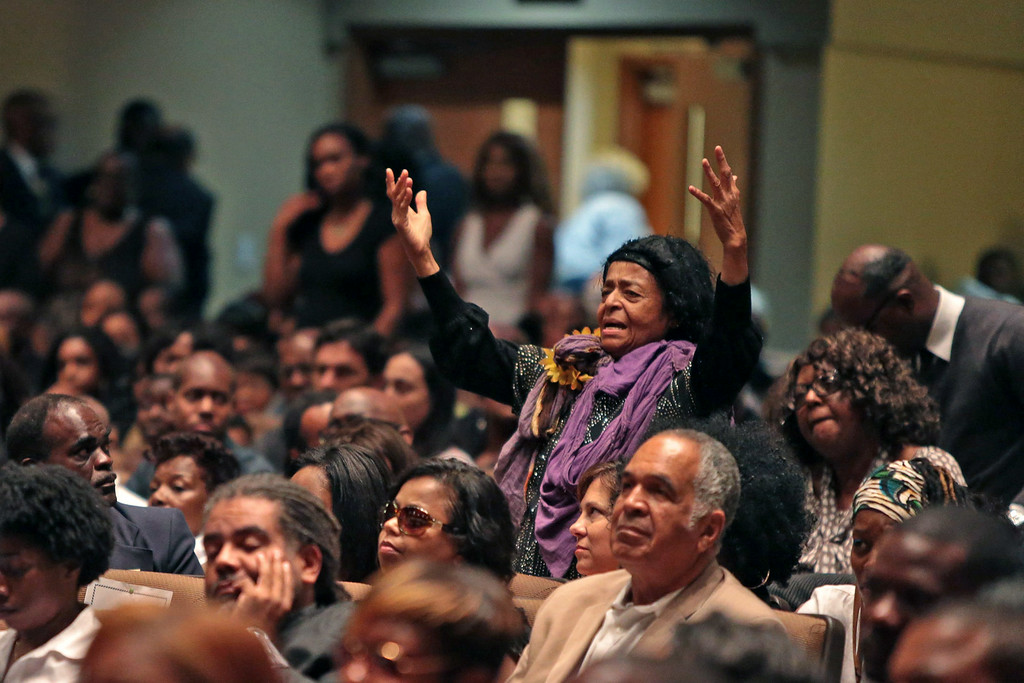 Description of . A woman rises to her feet during the funeral of Michael Brown inside Friendly Temple Missionary Baptist Church on August 25, 2014 in St. Louis Missouri. Michael Brown, an 18 year-old unarmed teenager, was shot and killed by Ferguson Police Officer Darren Wilson in the nearby town of Ferguson, Missouri on August 9. His death caused several days of violent protests along with rioting and looting in Ferguson.  (Photo by Robert Cohen-Pool/Getty Images)