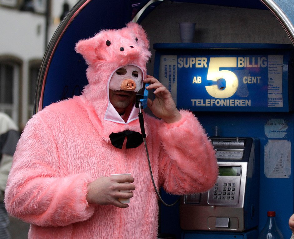 """Description of . A carnival  reveller dressed as a pig uses a phone during the start of the street-carnival with its tradition of fools entering the town halls and women cutting off men\'s ties with scissors on carnival\'s so called \""""Old Women\'s Day\"""" in Cologne, Germany, Thursday, Feb. 7, 2013. The \""""Old Women\'s  Day\""""  is traditionally the beginning of  street carnival, the foolish street spectacles in the carnival centers of Duesseldorf, Mainz and Cologne. Advertising reads: Super Cheep, calls up from 5 euro cents (6.9 US cents). (AP Photo/Frank Augstein)"""