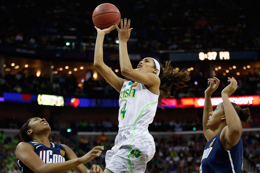 Description of . Skylar Diggins #4 of the Notre Dame Fighting Irish makes a shot over Morgan Tuck #3 of the Connecticut Huskies during the National Semifinal game of the 2013 NCAA Division I Women\'s Basketball Championship at the New Orleans Arena on April 7, 2013 in New Orleans, Louisiana.  (Photo by Chris Graythen/Getty Images)