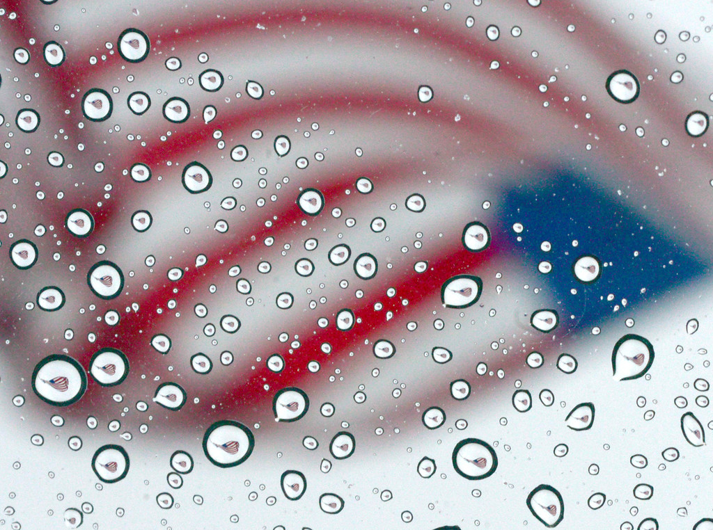 Description of . An American flag flying at Uptown Station shopping center is reflected in rain drops on Thursday, July 4, 2013 in Fort Walton Beach, Fla. (AP Photo/Northwest Florida Daily News, Nick Tomecek)