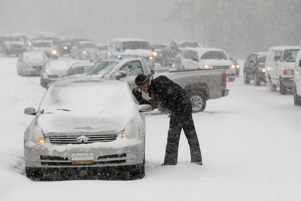 Description of . A Highway Patrol officer checks on the safety of a stranded motorist on Hammond Road during a winter storm Wednesday Feb. 12, 2014, in Raleigh, N.C. (AP Photo/The News & Observer, Travis Long)