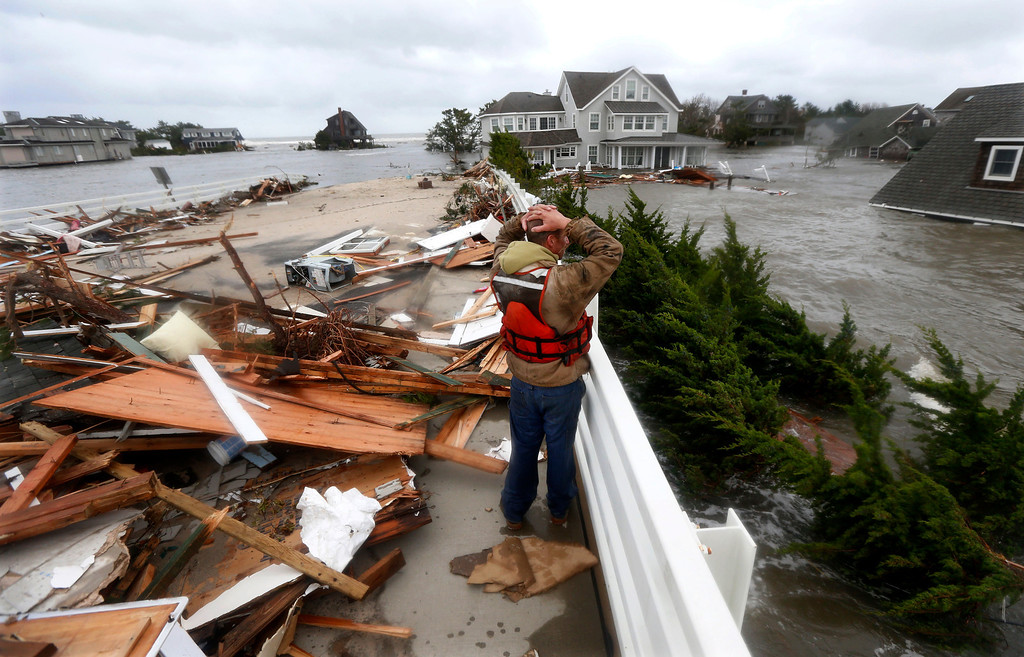Description of . In this Oct. 30, 2012 file photo, Brian Hajeski, 41, of Brick, N.J., reacts as he looks at debris of a home that washed up on to the Mantoloking Bridge the morning after superstorm Sandy rolled through in Mantoloking, N.J. Sandy, the storm that made landfall, caused multiple fatalities, halted mass transit and cut power to more than 6 million homes and businesses. (AP Photo/Julio Cortez, File)