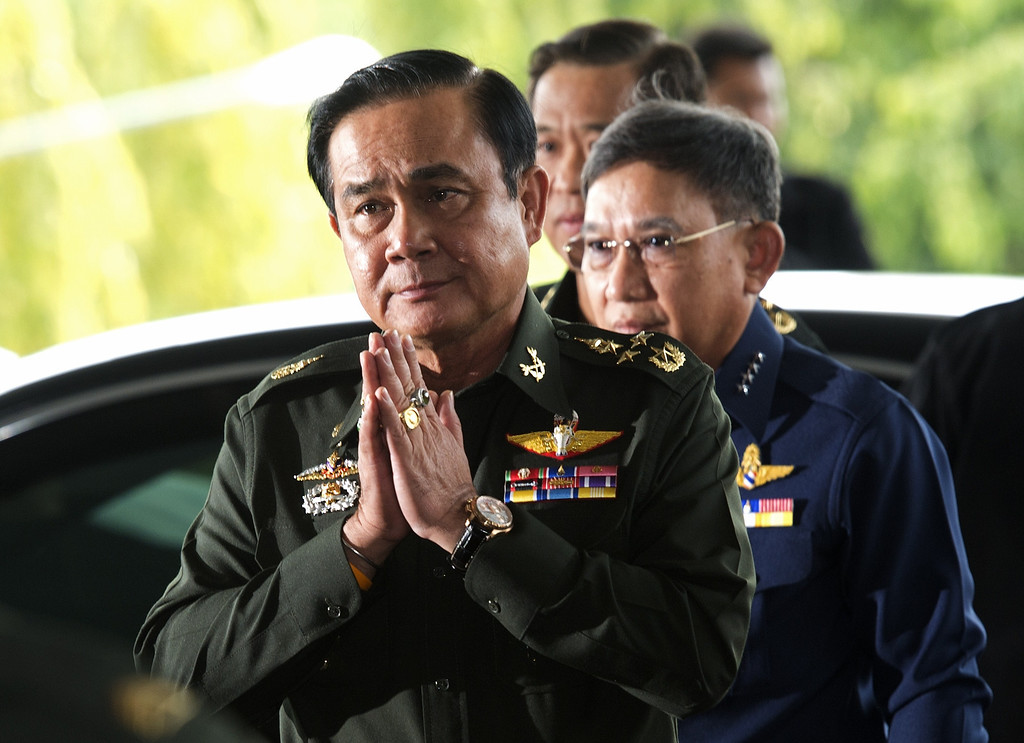 Description of . Thai army chief General Prayut Chan-O-Cha gives a traditional greeting to delegates prior to a meeting at the Army Club in Bangkok on May 20, 2014. Thailand's army declared martial law after months of deadly anti-government protests, deploying armed troops in central Bangkok and censoring the media but insisting the move was