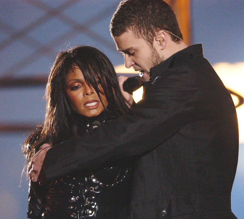 Description of . Justin Timberlake reaches across Janet Jackson during their performancs just before he pulled off the covering to her right breast, which was partially obscured by a sun-shaped, metal nipple decoration during the half time performance at Super Bowl XXXVIII in Houston, Sunday Feb. 1, 2004. (AP Photo/David Phillip)