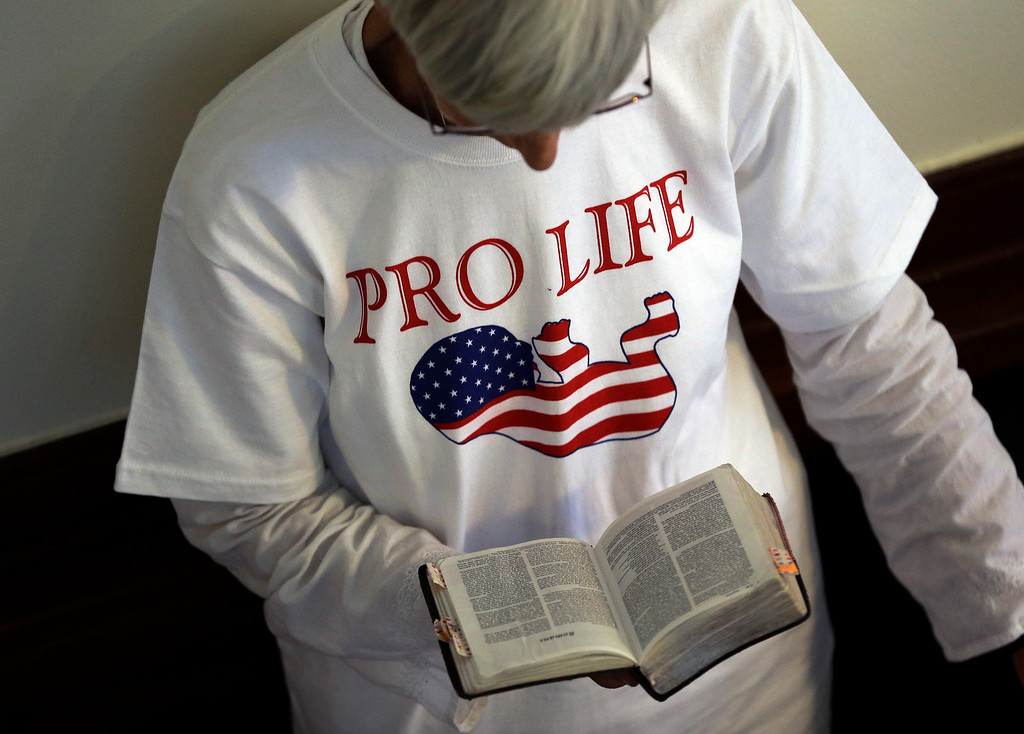 Description of . A supporter an abortion bill reads the Bible while in line outside the Texas Senate chambers as he final vote by the Senate is expected to begin, Friday, July 12, 2013, in Austin, Texas. The bill would require doctors to have admitting privileges at nearby hospitals, only allow abortions in surgical centers, dictate when abortion pills are taken and ban abortions after 20 weeks. (AP Photo/Eric Gay)
