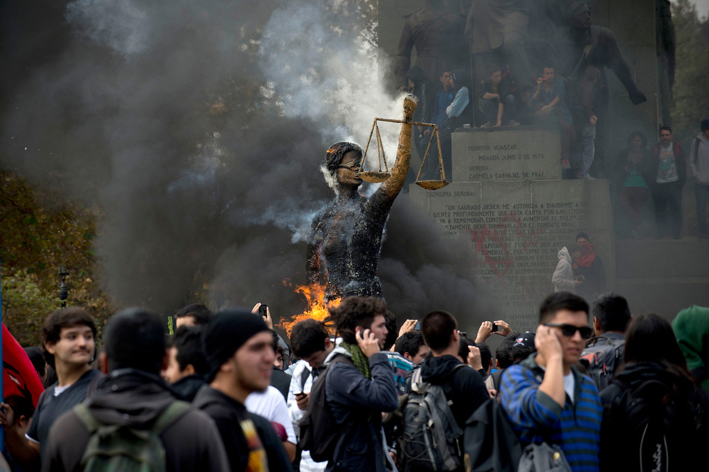 Description of . Students burn an efigy representing the Justice during a protest to demand Chilean President Sebastian Pinera\'s government to improve the public education quality, in Santiago, on April 11,2013. MARTIN BERNETTI/AFP/Getty Images