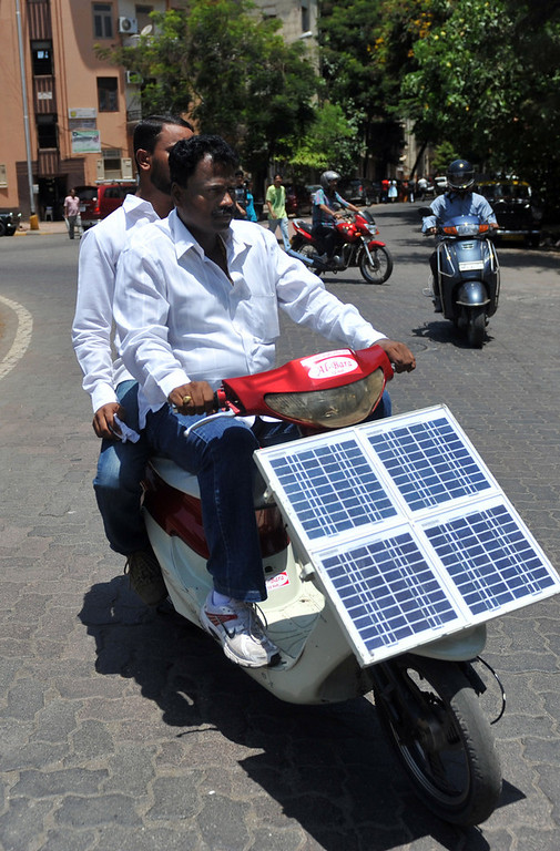 Description of . Ayub Khan Pathan drives his nephew Imran Khan Pathan drives a self-made electric scooter in Mumbai on May 31, 2011. The duo spent three years transforming a second-hand scooter into an eco-friendly solar powered vehicle. The solar powered bike cost 27,000 Indian rupees (415 euros) to build and can cover a distance of approximately 60 kms with a single full charge. AFP PHOTO / Sajjad HUSSAIN