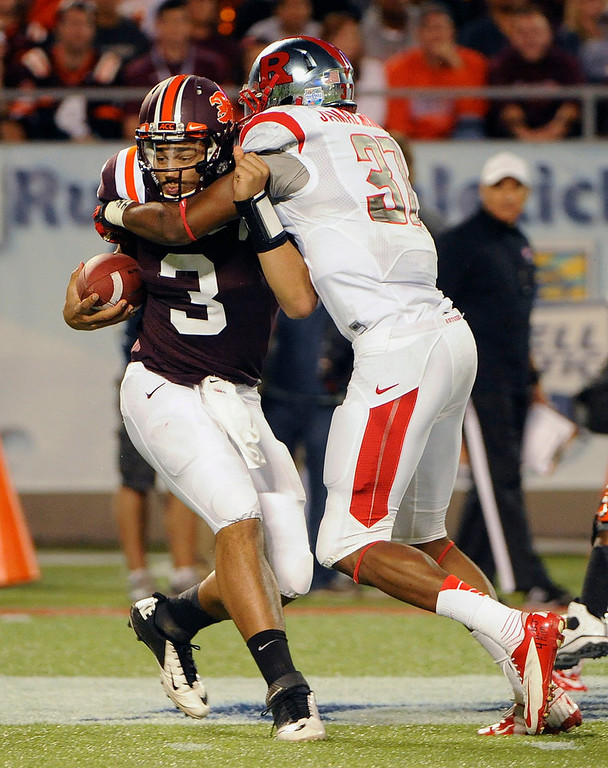 Description of . Virginia Tech quarterback Logan Thomas, left, is sacked for a loss of eight yards by Rutgers linebacker Jamal Merrell during the first quarter of an NCAA college football Russell Athletic Bowl game on Friday, Dec. 28, 2012, in Orlando, Fla. (AP Photo/Brian Blanco)