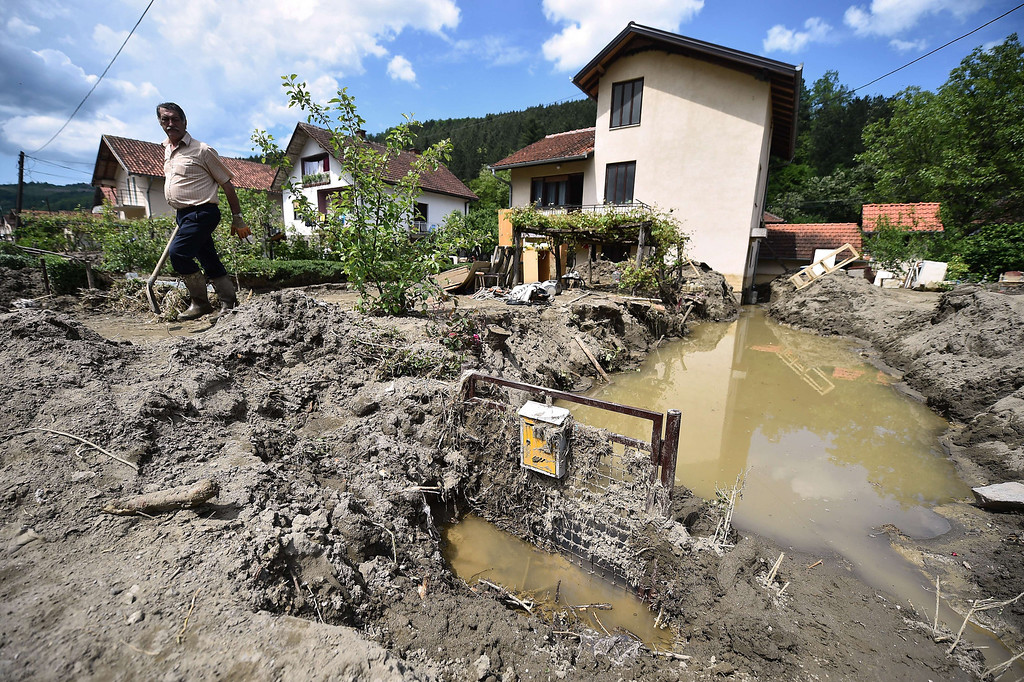 Description of . A man walks out from his mud covered front yard in Krupanj, some 130 kilometers south west of Belgrade, on May 20, 2014, after it was hit with floods and landslides, cutting the western Serbian town off for four days. Serbia declared three days of national mourning on May 20 as the death toll from the worst flood to hit the Balkans in living memory rose and health officials warned of a possible epidemic.   AFP PHOTO / ANDREJ  ISAKOVIC/AFP/Getty Images