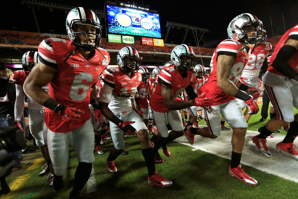 Description of . MIAMI GARDENS, FL - JANUARY 03: The Ohio State Buckeyes run onto the field during warm ups prior to the Discover Orange Bowl against the Clemson Tigers at Sun Life Stadium on January 3, 2014 in Miami Gardens, Florida.  (Photo by Chris Trotman/Getty Images)