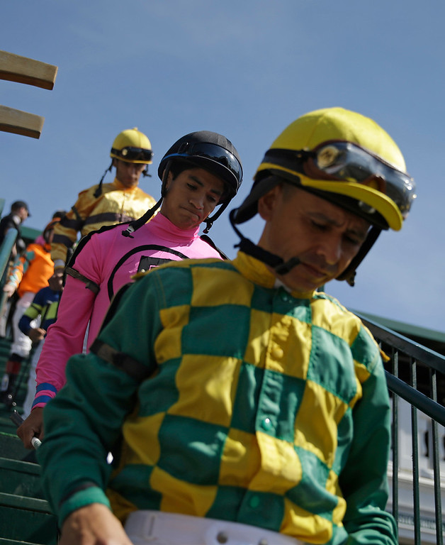 Description of . Jockeys walk into the paddock before a race before the 140th running of the Kentucky Derby horse race at Churchill Downs Saturday, May 3, 2014, in Louisville, Ky. (AP Photo/David Goldman)