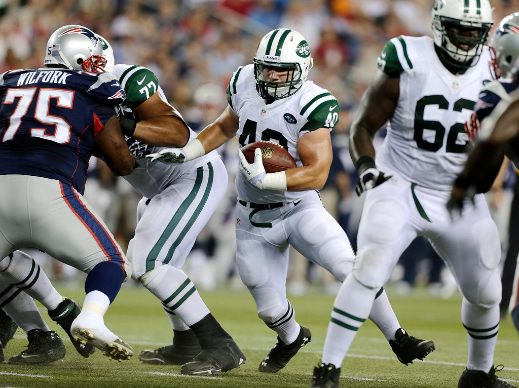 Description of . New York Jets fullback Tommy Bohanon (40) looks for running room next to New England Patriots defensive tackle Vince Wilfork (75) during the first quarter of an NFL football game Thursday, Sept. 12, 2013, in Foxborough, Mass. (AP Photo/Charles Krupa)