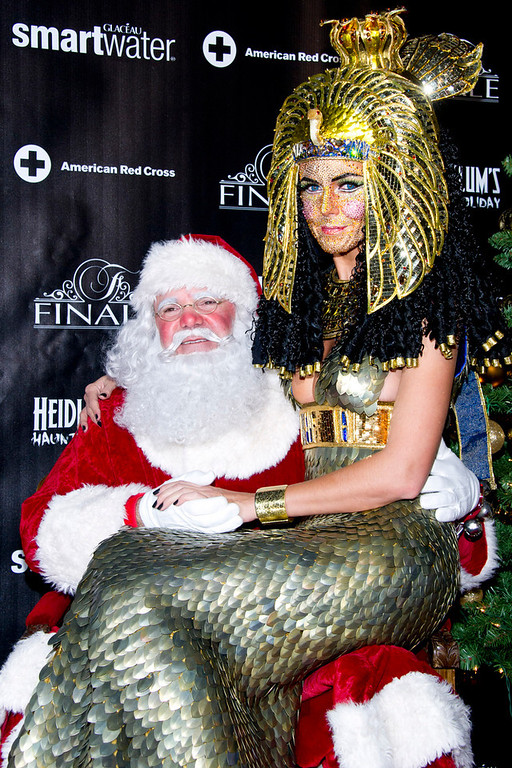 Description of . Heidi Klum, dressed as Cleopatra, poses with Santa Claus during her Haunted Holiday Party benefiting Superstorm Sandy relief efforts, on Saturday, Dec. 1, 2012 in New York. Klum's original party, scheduled to be held on Halloween, was postponed due to the storm. (Photo by Charles Sykes/Invision/AP)