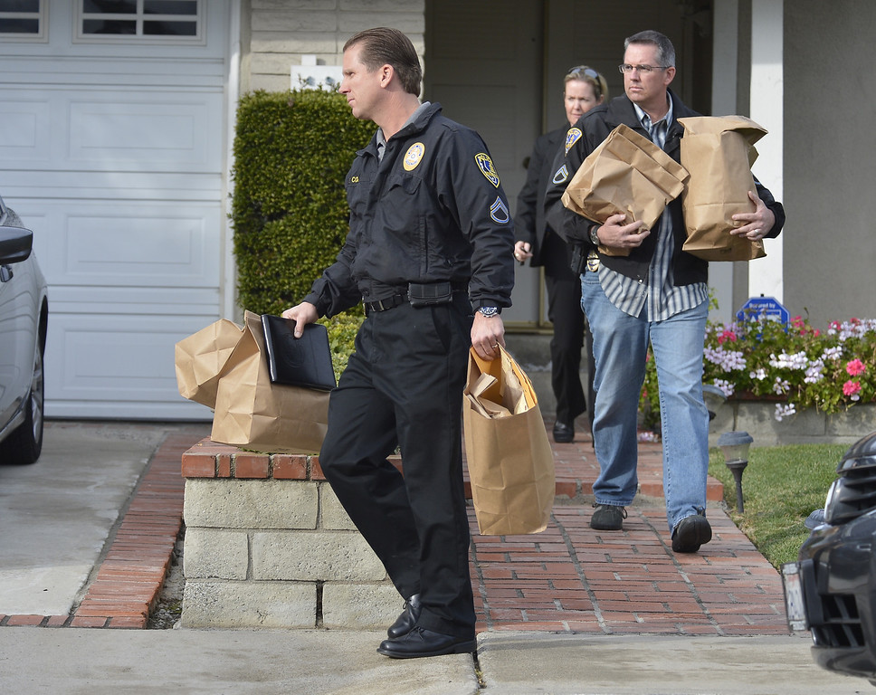 Description of . LA PALMA, CALIF. -- Investigators leave the home of the mother of alleged triple-murderer  Christopher Dorner in La Palma, California on February 8, 2013. Photo by Jeff Gritchen / Los Angeles Newspaper Group